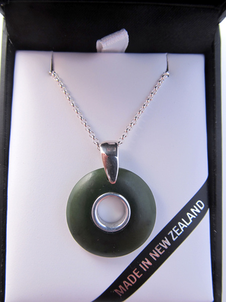 1022 Round doughnut shaped greenstone pendant (2.1cm) with silver inlay.