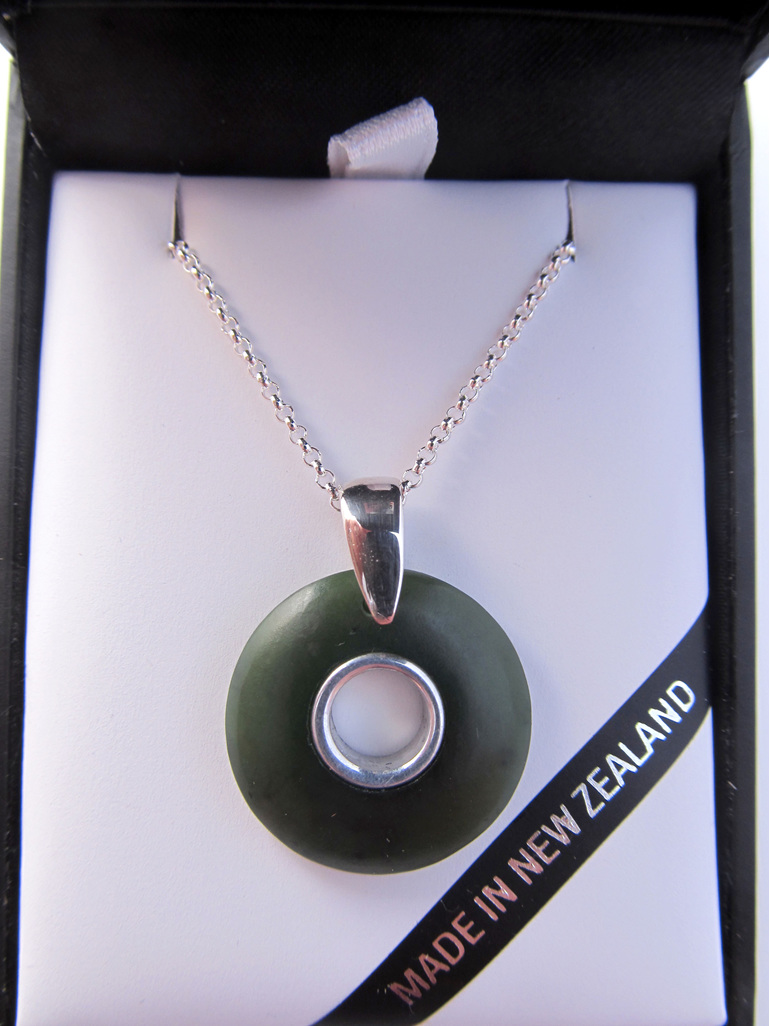 1022 Round doughnut shaped greenstone pendant with silver inlay.