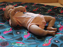 Baby girl relaxing on a babybaby padded play mat designed by BabyBaby