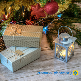 Beautifully wrapped Xmas gifts sit under a decorated tree on a wooden floor.