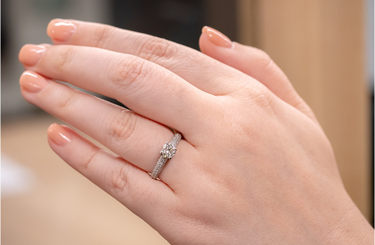 Brilliant cut four claw solitaire with pave set diamond band