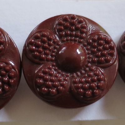 Three matching brown glass buttons