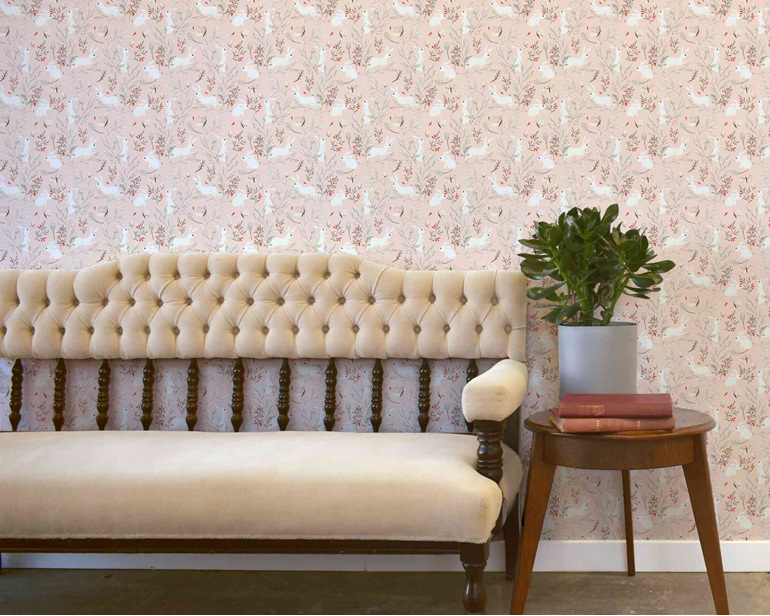 Bunny wallpaper on pink background with velvet couch, table and plant