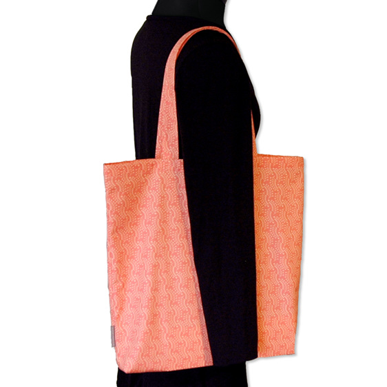 carry pouch peach colour reusable cotton shopping bag being worn