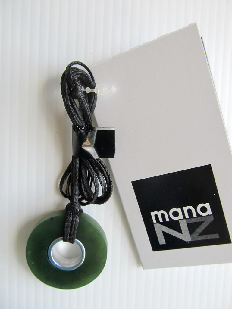 CKA964 Greenstone doughnut shaped pendant on black cord.