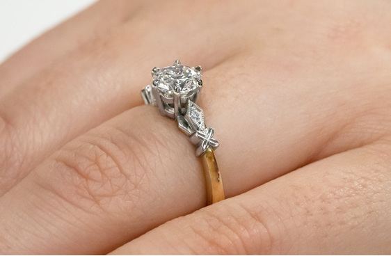 Close up celtic pattern solitaire diamond engagement ring yellow gold platinum