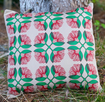 Cushion cover with Pohutukawa flowers on Dusk coloured fabric.