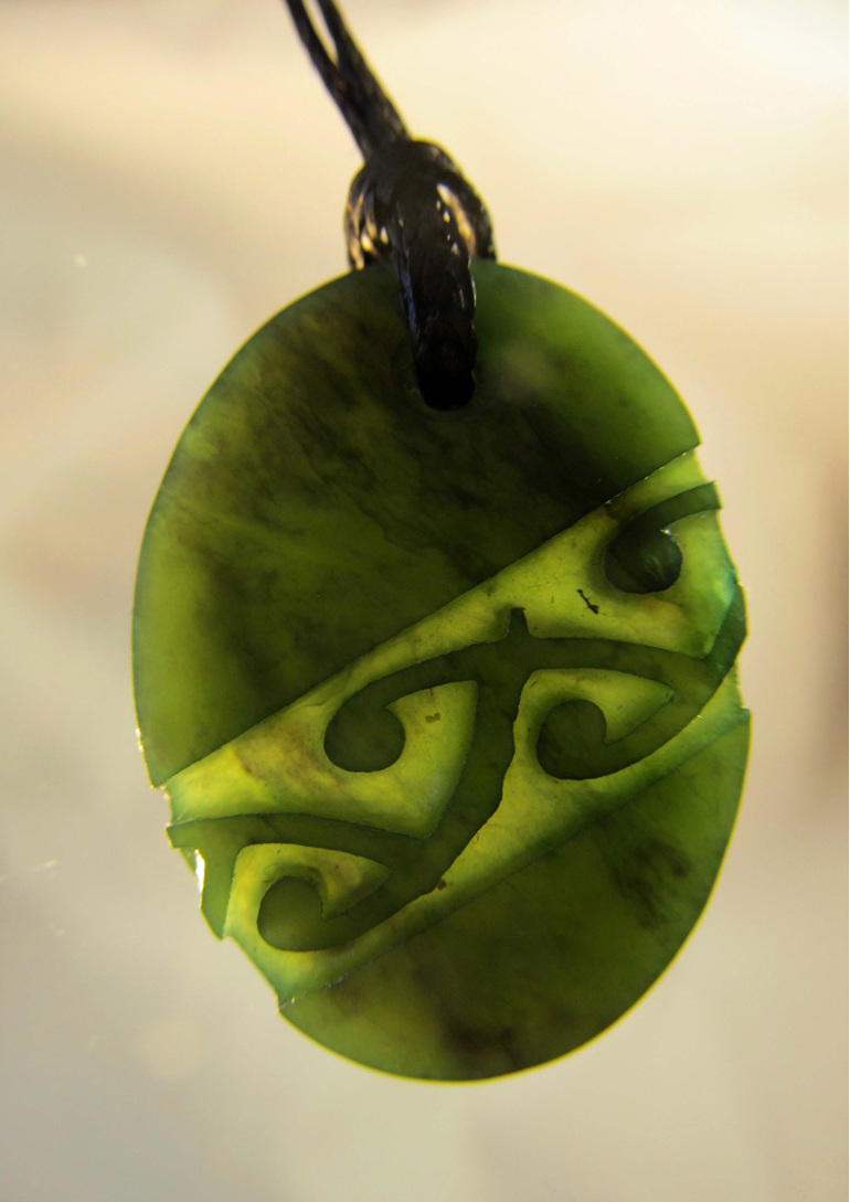D123 Oval greenstone pendant with diagonal pattern and black cord.