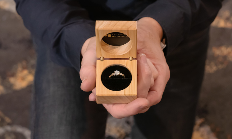 engagement ring in proposal box with man holding it while on one knee