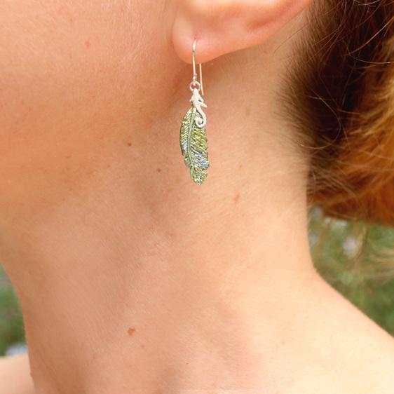 feather kereru bird green blue white koru iridescent earring worn