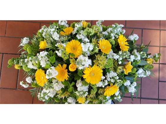 Flowerise designed casket spray in bright yellows