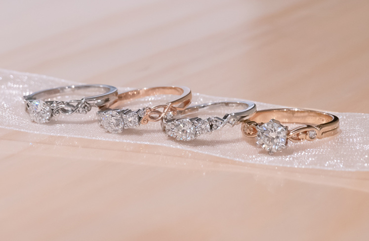 Four rings from the narrative collection, in both white and rose gold.