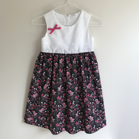 Girls summer dress:  White broderie bodice with black and pink bicycles. - SIZE 5