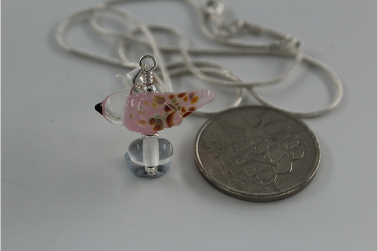 Glass bird pendant - pink opalino with NZ 50 cent piece for size reference