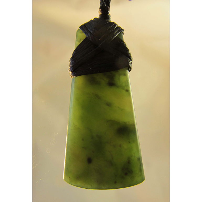 Greenstone wedge shaped pendant or toki bound with waxed cord.