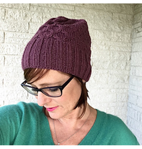 image is a female wearing a beanie with cable pattern looking downwards