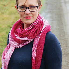 image is of a woman wearing a bright pink and pale pink knitted scarf