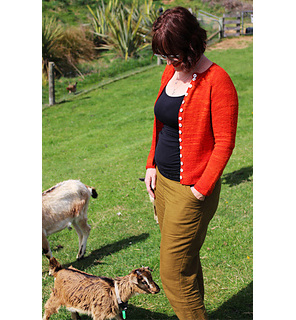 image is of a woman wearing an orange cardigan with head down looking at 2 goats