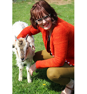 image is of female wearing an orange cardigan crouched down with arm around goat