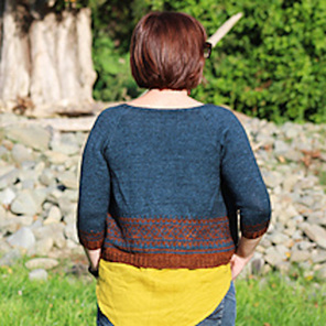 image is of female with back turned to camera wearing a blue and rust cardigan