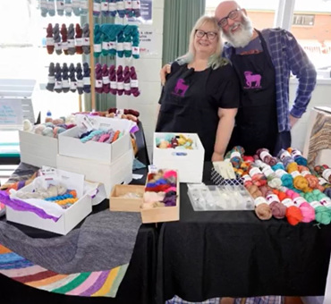 image shows a blonde haired lady and a bearded man standing behind a yarn stall
