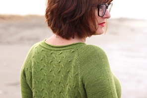image shows a female with body half turned wearing a green hand knit sweater