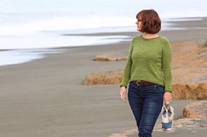 image shows a female with head turned wearing a green hand knit sweater