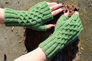 image shows a pair of hands wearing green knit fingerless mittens with cables