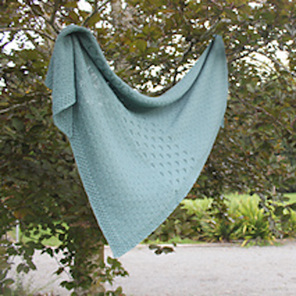 image shows a pale teal shawl with cables hanging in a tree