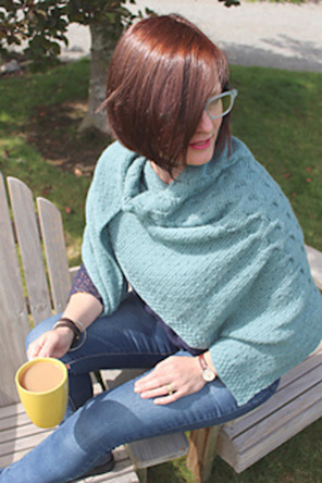 image shows a person sitting down holding a cup of tea wearing a pale teal shaw