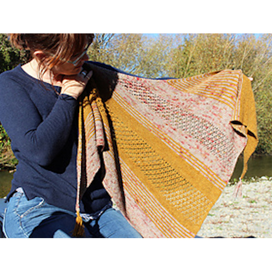 image shows a woman holding a triangle  shawl in golden yellow and red speckles