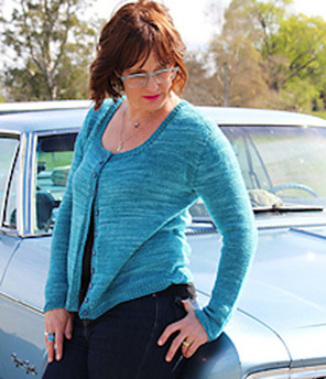 image shows female leaning on a car wearing an aqua coloured scoop neck cardigan