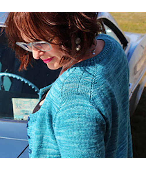 image shows head and shoulder of female wearing an aqua coloured knit cardigan