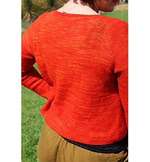 image shows the back of a person wearing a bright orange hand knit cardigan