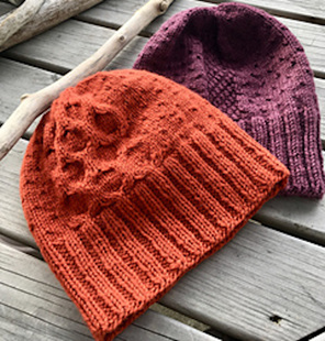 image shows two beanies, one orange, one maroon laid side by side on a wood deck