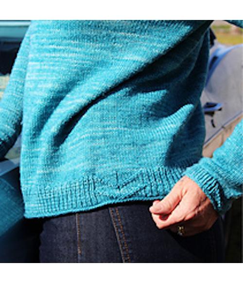 images is the lower half of a torso wearing an aqua knit cardigan arrows on hem