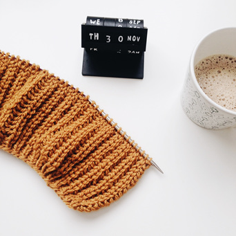Images shows knitting, a desk calendar and a drink in a mug