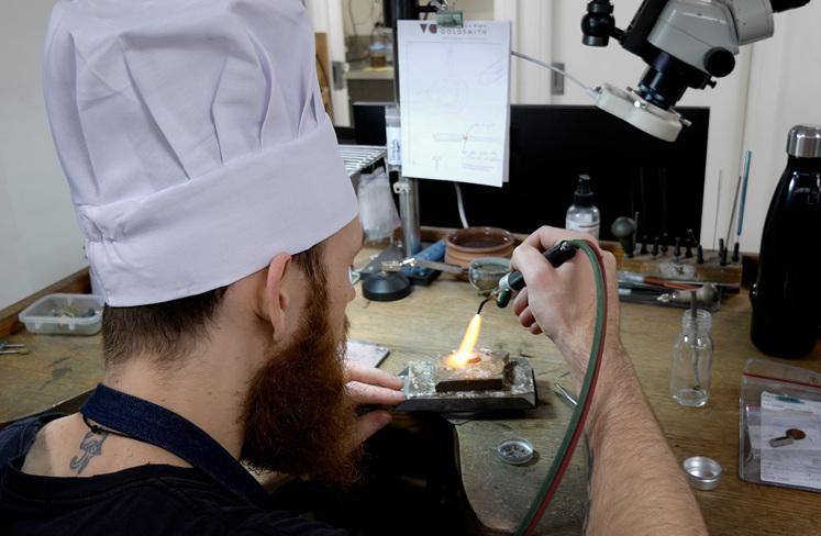 Jeweller crafting frying pan pendant wearing chef hat in jewellery workshop