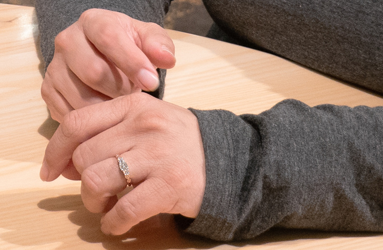 Julia's hand with her new Baile three-stone diamond engagement ring