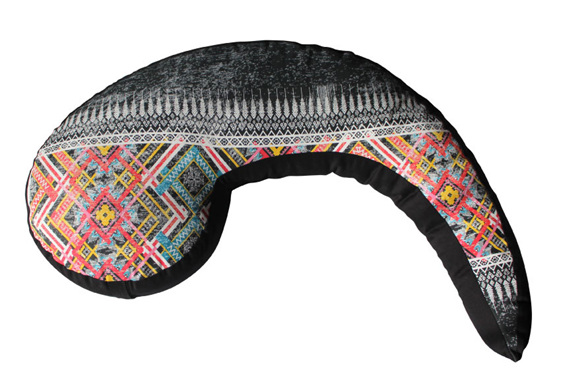 Koru shaped nursing pillow with vibrent tribal designs over it