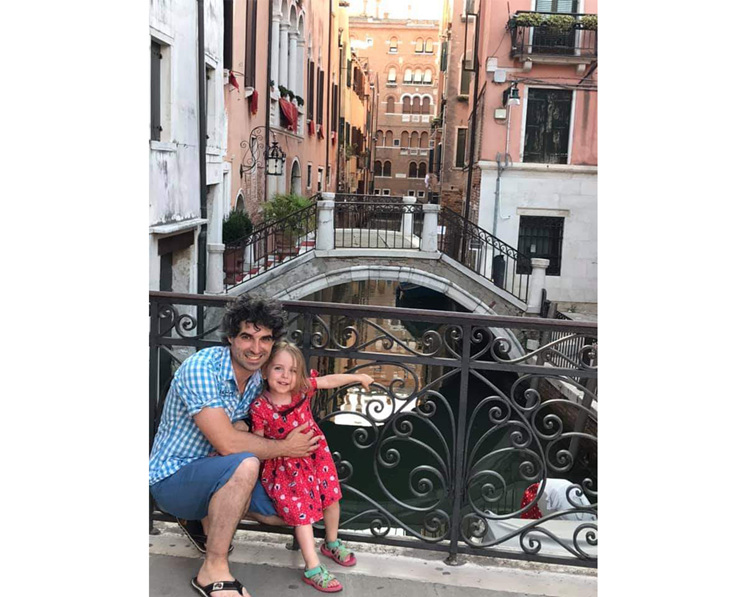 Man and girl in front of Venice canal bridge in Italy