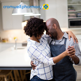 Man and woman both smiling dance romantically at home