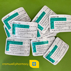 Multiple packs of Levlen contraceptive pill on a green background