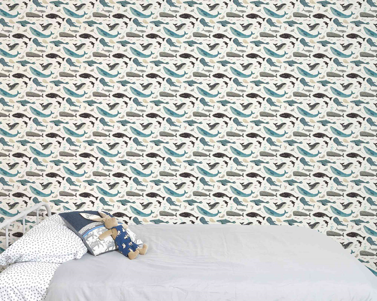 Ocean wallpaper with whales behind a bed and velveteen rabbit