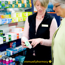 Pharmacist explains the instructions on a box of medicine to an elderly lady