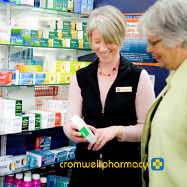 Pharmacist is explaining to a customer the instructions on the medication label.