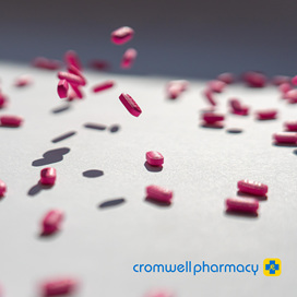Pink oval pills are falling through the air onto a white surface.