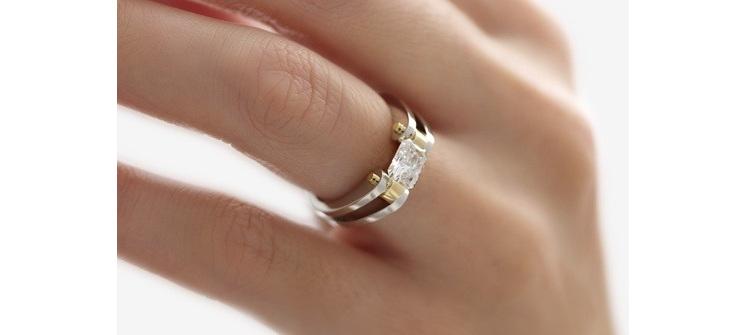 Platinum and gold diamond ring with a tension set rectangular radiant diamond
