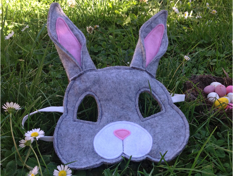 Rabbit mask in the grass with easter eggs and daisies.
