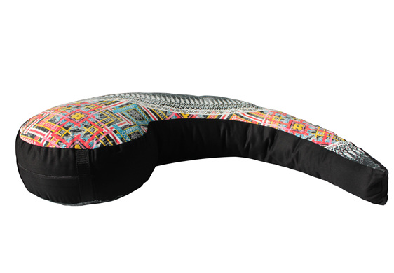 Side view of a Koru shaped nursing pillow with vibrent tribal designs over it